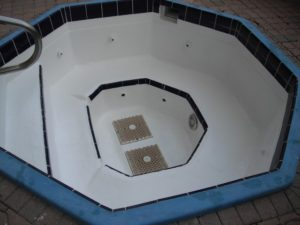 The Waves condominium hot tub midway through renovation by Pristine Pool Coatings Of South Florida.
